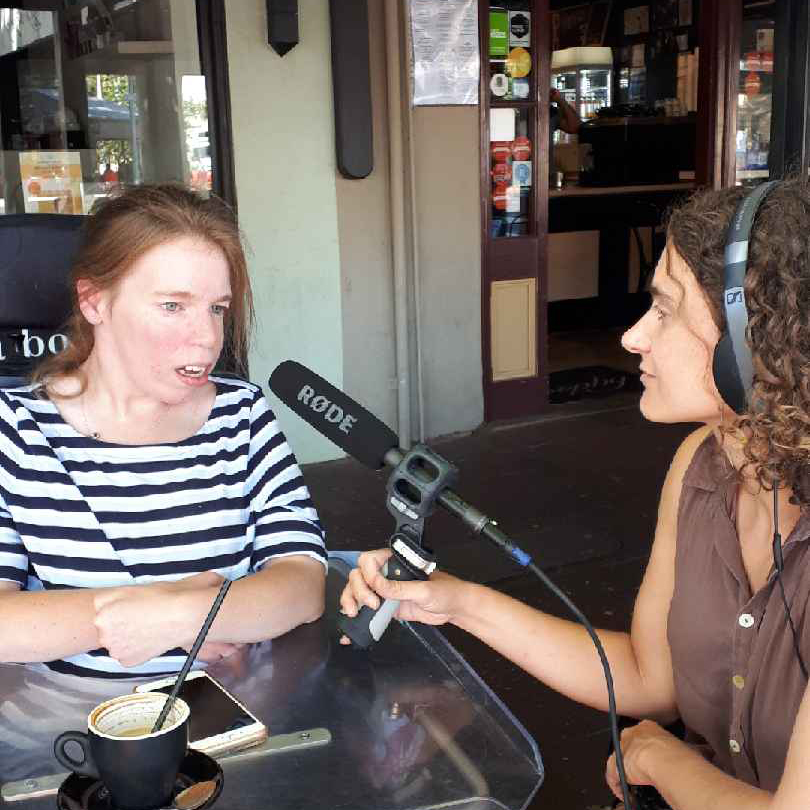 Georgia Horgan being interviewed at cafe while drinking a coffee with a straw
