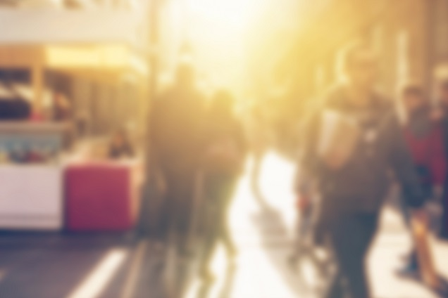 Blurred photo of people walking on a street on a sunny day.