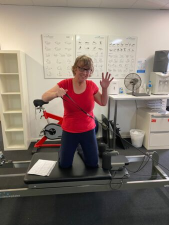 Jane having fun in her pilates class. She is kneeling down on a pilates reformer and waving to the camera.