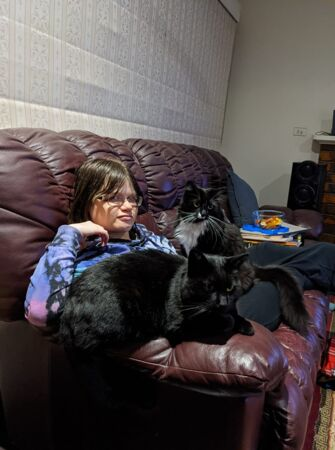 Leeanne relaxing on her couch at home with her two cats.