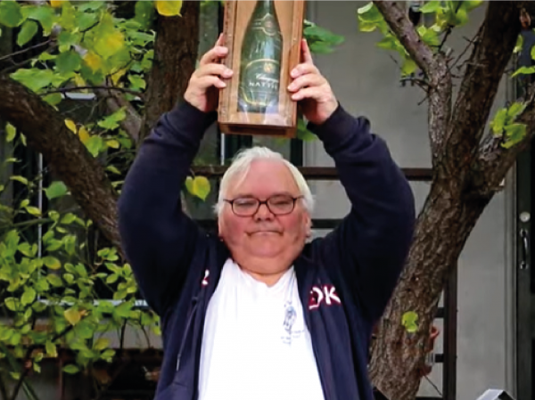 Image is Collin holding the champagne bottletrophy over his head in victory.